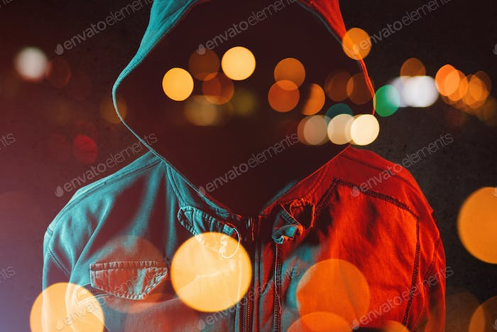 Faceless hooligan with hoodie in urban surrounding