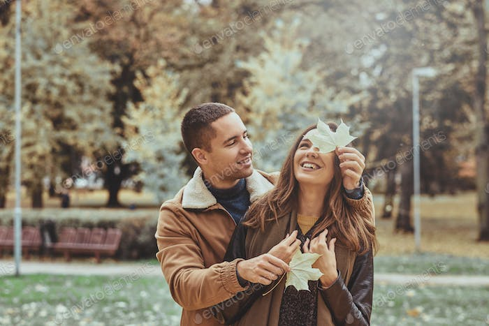 Romantic couple have fun with autumn leaf