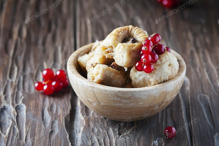 Baklava with red currant on the wooden table