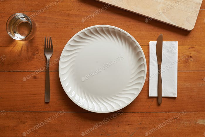 Porcelain plate and cutlery against a wood background