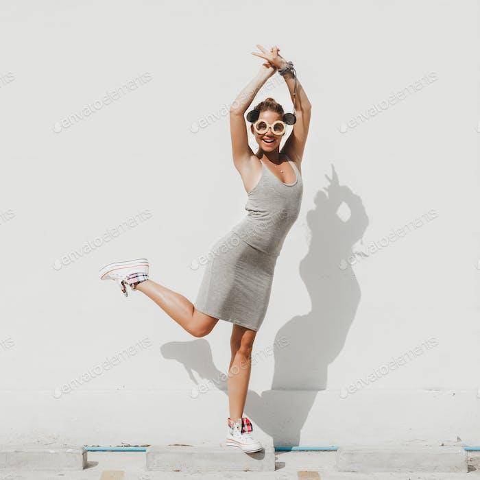 Girl having fun on gray wall background