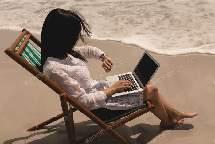 Young woman relaxing on sun lounger and looking smartwatch while using laptop on beach