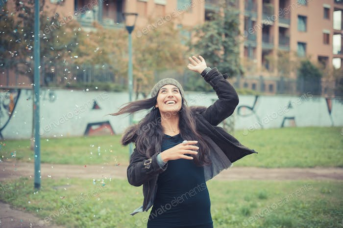 young beautiful brunette woman playing with confetti carnival