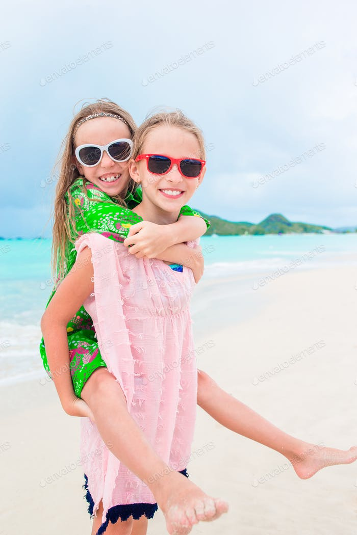Little happy kids have a lot of fun at tropical beach playing together