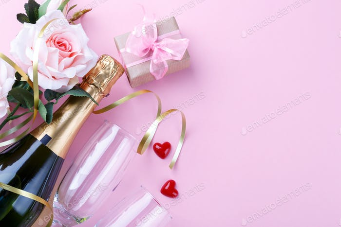 Bottle of champagne on pink background