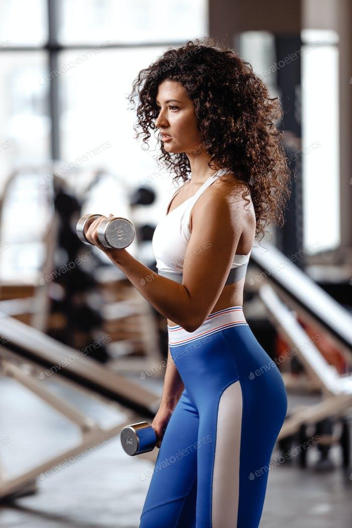 Schlankes Mädchen mit dunklen lockigen Haaren in einer Sportbekleidung gekleidet macht Übungen mit Hanteln in der