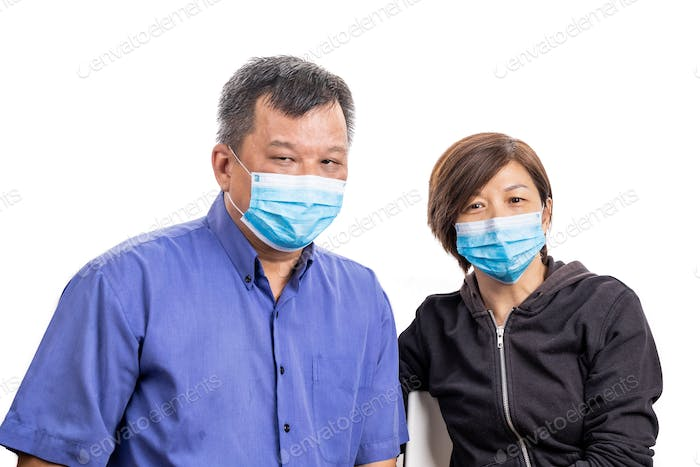 Concerned mature Asian Chinese couple with face mask for protection against influenza virus