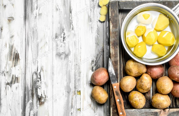 Peeled potatoes in a saucepan with unpeeled potatoes on tray with a knife.