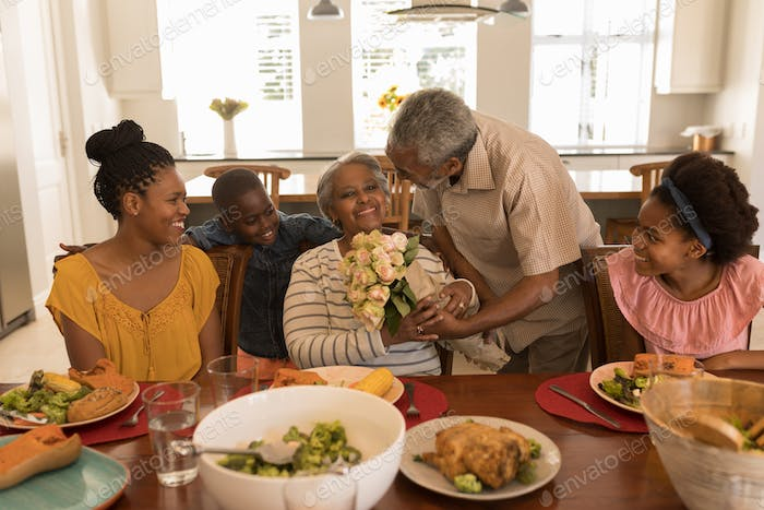 African American senior man giving a beautiful flower bouquet to his wife