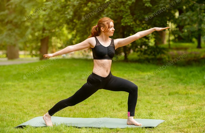 Fit red haired girl doing warrior yoga pose during her outdoor class at park