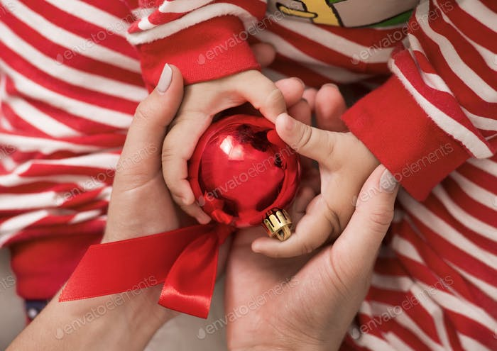 Baby and mother holding red Christmas ball in hands