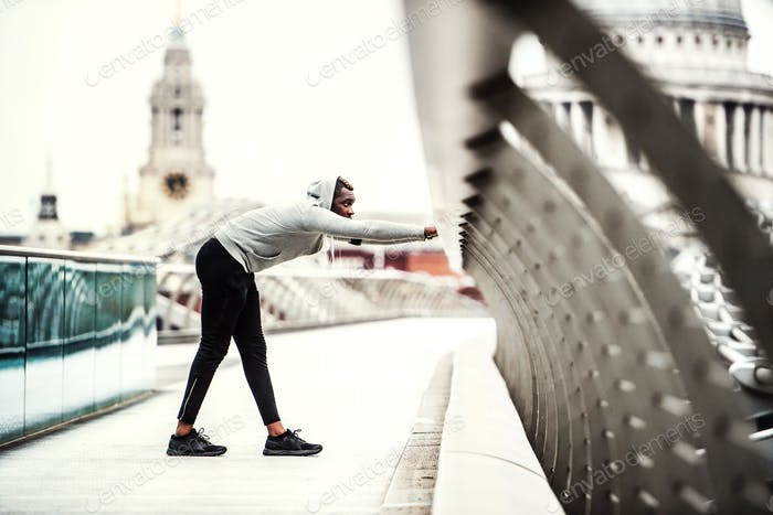 Black man runner on the bridge in a city, stretching.