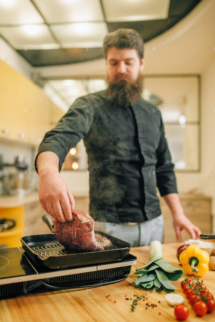 Bearded chef cooking meat in a pan on the kitchen