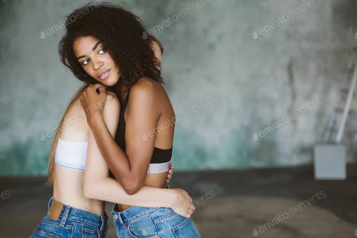 Young beautiful african american woman with curly dark hair in t