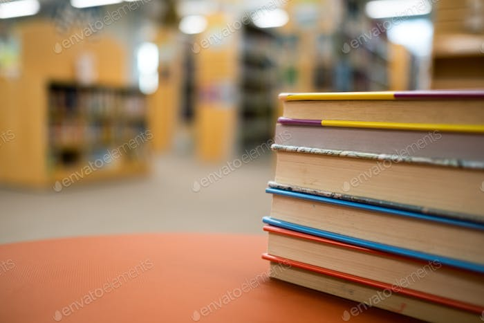Stack of books on a wooden table in a library