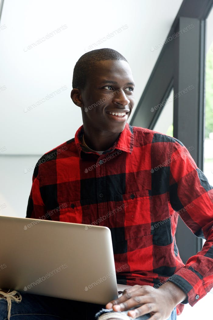 Happy young african man sitting outdoors with laptop
