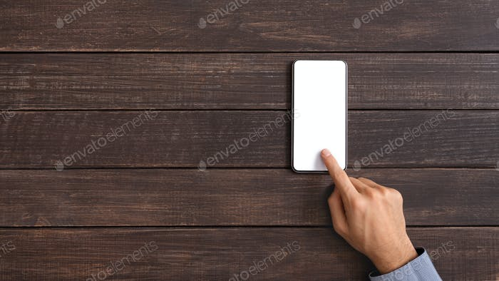 Male hand touching blank smartphone screen over dark wooden background