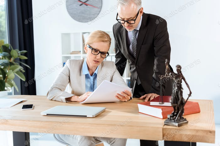 serious mature lawyers with paperwork in modern office