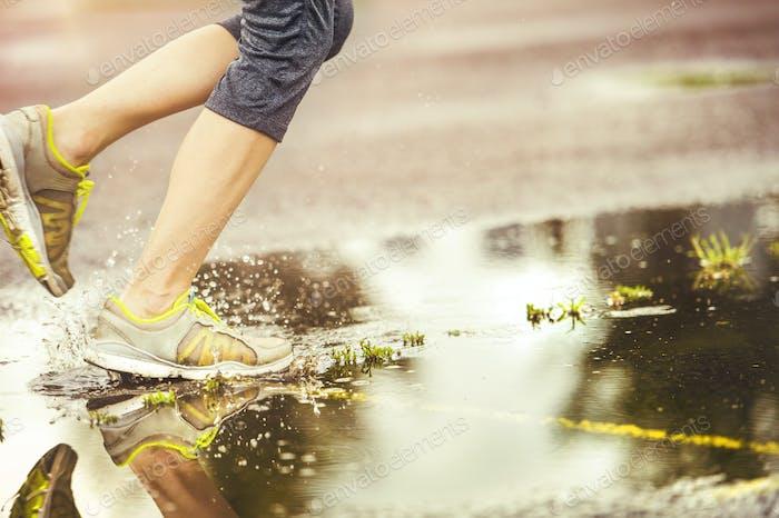 Junge Frau läuft bei Regenwetter