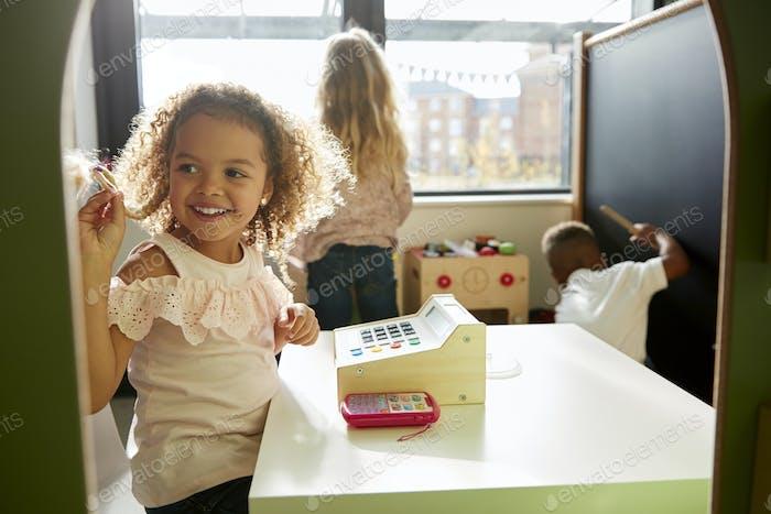 Zwei junge Schulmädchen und ein Junge spielen zusammen in einem Spielhaus in der Kinderschule, hinterleuchtet