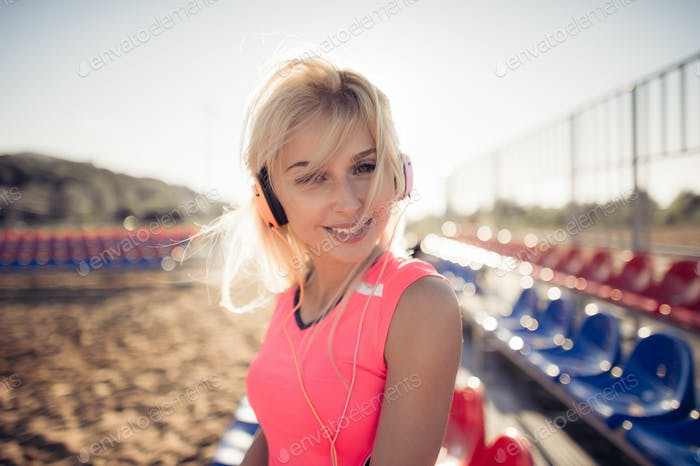 Smiling beach volleyball female player portrait with earphones.