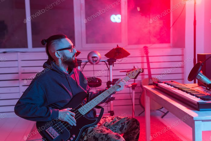 Create music and a recording studio concept - Bearded funny man guitarist recording electric bass
