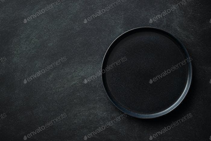 Empty Black Plate on Black Table.