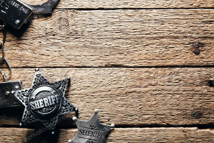 Sheriff star and handcuffs on wooden table