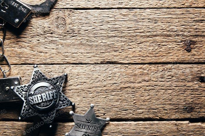 Sheriff Stern und Handschellen auf Holztisch