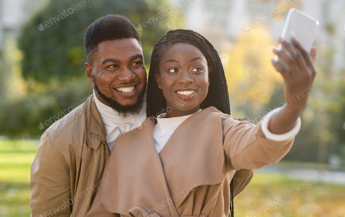Happy afro couple taking self-portrait, capturing their happy moments together