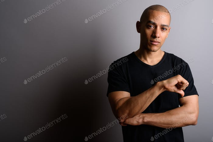 Handsome bald man giving thumb down against gray background