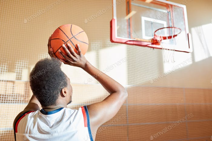 Rear view of determined basketball player throwing ball in baske