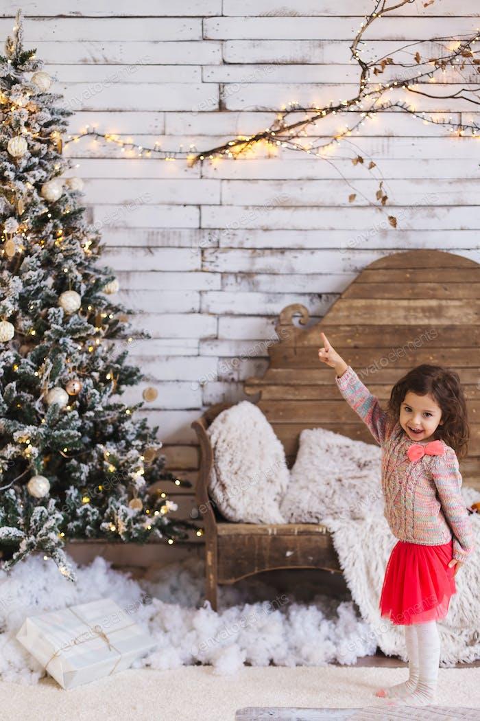 Забавная маленькая девочка, указывающая пальцем на вершину елки