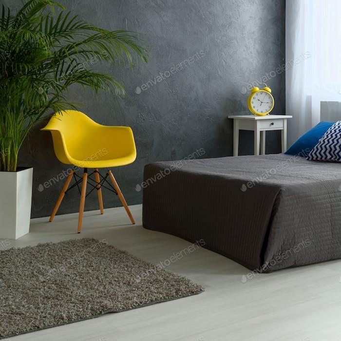 Graues Schlafzimmer mit gelbem Stuhl