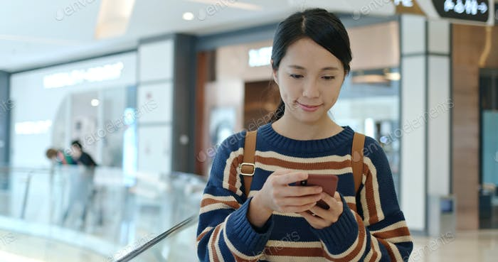 Woman check the sales on cellphone inside shopping center