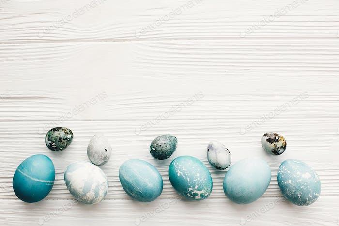 Stilvolle Ostereier auf weißem Holzhintergrund