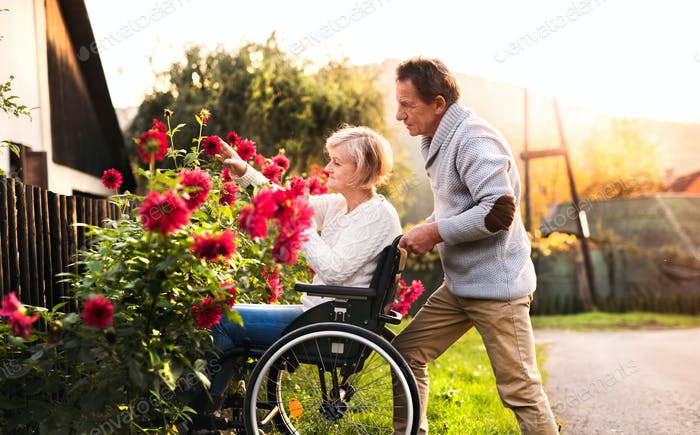 Senior couple with wheelchair on a walk.