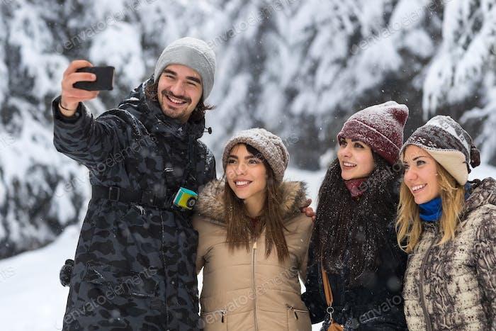 Hombre mantener la cámara del teléfono Inteligente Encantador selfie foto Amigos Sonrisa Bosque de Nieve Gente Grupo al aire libre