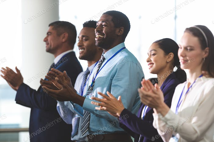 Business people applauding standing at business seminar in office building