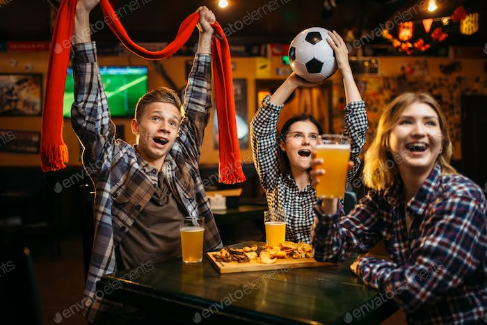 Football fans with scarf and ball in sports bar