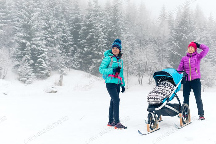 Happy family in mountains. Mother with baby stroller enjoying mo