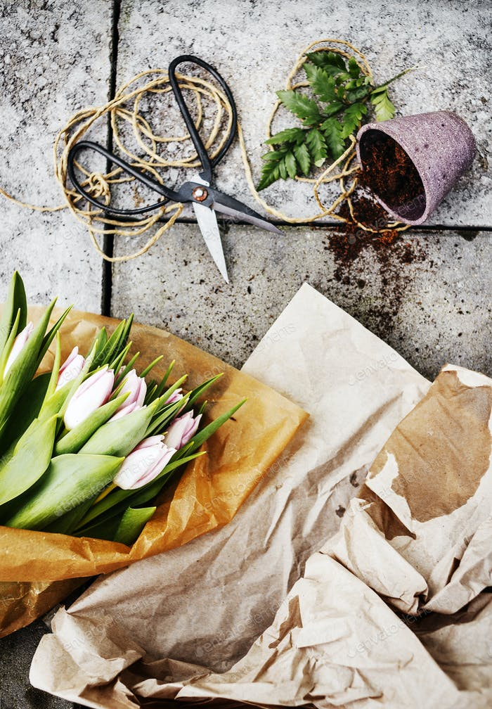 Directly above shot of tulip bouquet with scissors and pot on concrete floor
