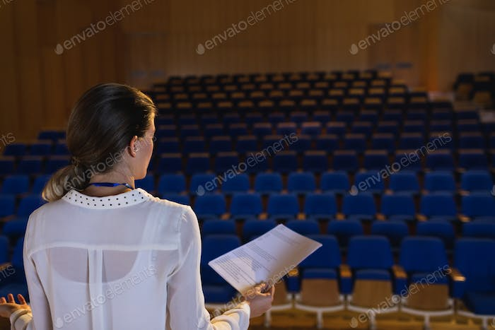 Blonde businesswoman practicing and learning script while standing in the auditorium