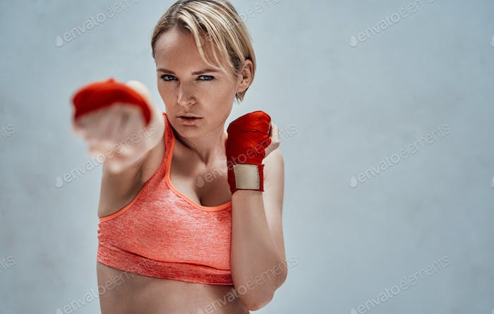Sportive adult female model with blonde hair and orange fitness bra posing in a bright room