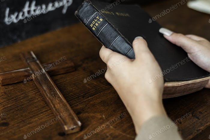 Hands Holding Holy Bible Next to Wooden Cross