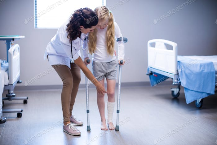 Female doctor assisting girl to walk with crutches in ward