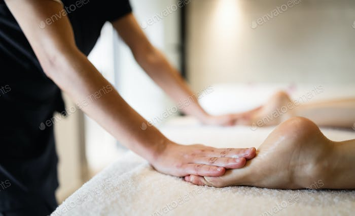 Masseuse masaging feet of person at massage