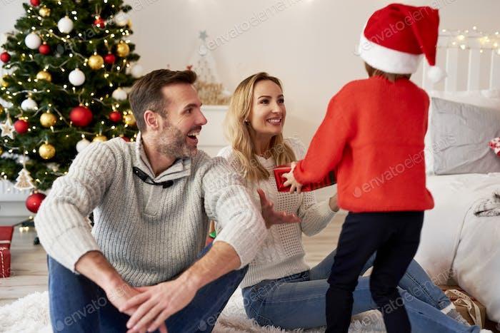 Mädchen geben ihren Eltern das Weihnachtsgeschenk