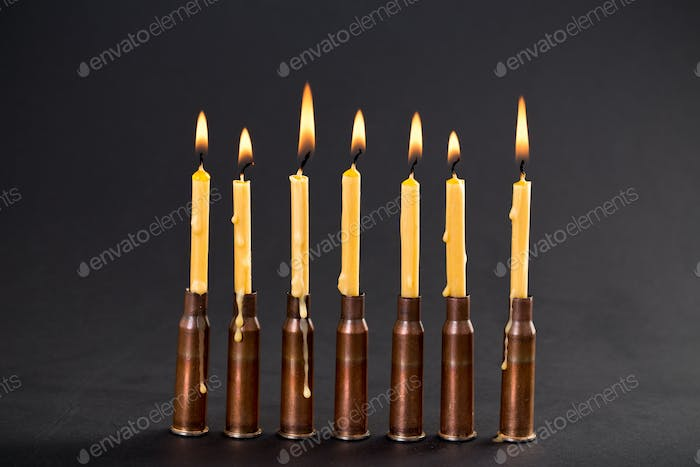 Burning candles and empty rifle cartridges.
