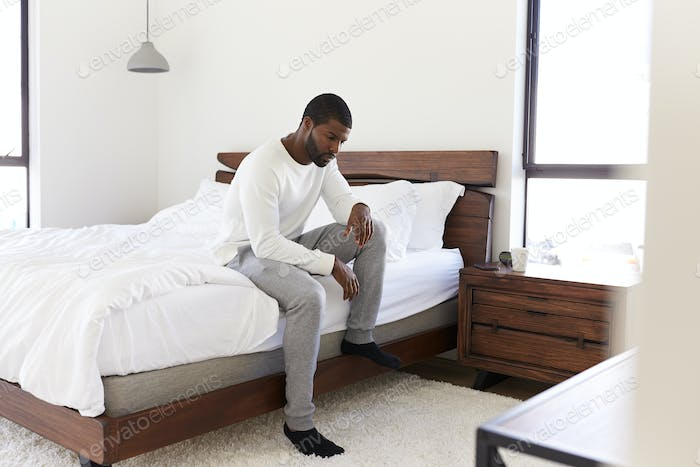 Thumbnail for Depressed Man Looking Unhappy Sitting On Side Of Bed At Home